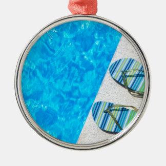 Zwei badenpantoffel auf Rand des Swimmingpools Silbernes Ornament