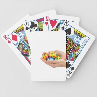 Zwei Hände, die gemalte Ostereier auf Weiß halten Spielkarten