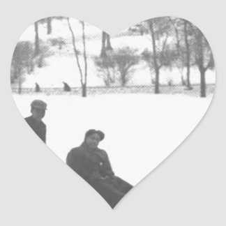 Zwei Jungen, die zwei Mädchen auf Schlitten ziehen Herz-Aufkleber