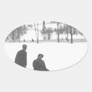 Zwei Jungen, die zwei Mädchen auf Schlitten ziehen Ovaler Aufkleber