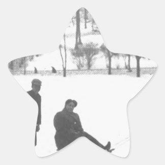 Zwei Jungen, die zwei Mädchen auf Schlitten ziehen Stern-Aufkleber