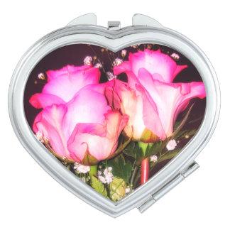 Zwei rosa Rosen mit Atem-Vertragsspiegel des Babys Schminkspiegel