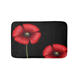 Zwei rote Mohnblumen-Blumen auf schwarzer Badematte
