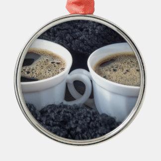 Zwei weiße Schalen mit schwarzem Kaffee und Schaum Rundes Silberfarbenes Ornament