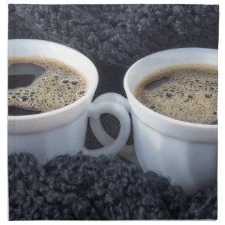 Zwei weiße Schalen mit schwarzem Kaffee und Schaum Serviette
