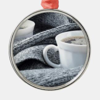 Zwei weiße Tasse Kaffees eingewickelt im Schal Rundes Silberfarbenes Ornament